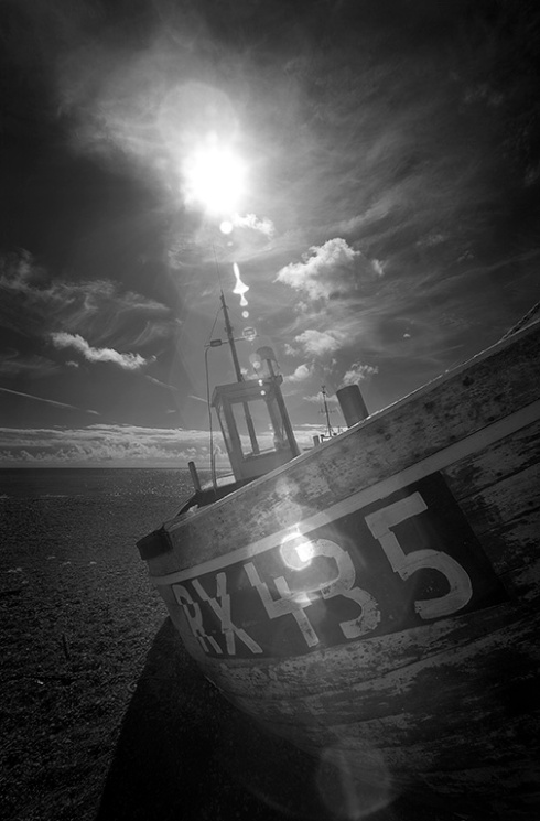 The sun shines on a dead boat.